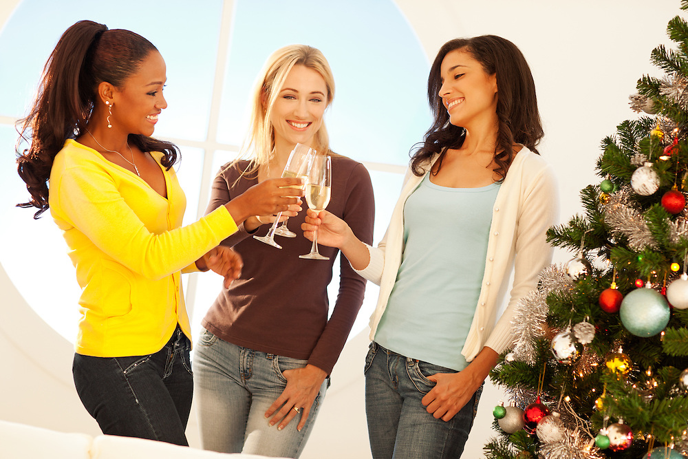 Three girlfriends standing by the Christmas tree and drinking champagne.