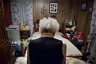 "Thelma Trout watches her cousin Doris Harrah and Doris' husband Glen arrange an electric blanket they brought for Trout's bed. The Harrahs live 15 minutes away in Little Hocking, Ohio, and visit Trout regularly. Trout also enjoys visits from friends, a welfare aide that cleans her house twice a week, and volunteers from Good Works who made repairs to her kitchen.  ""I'm doin' great by myself,"" says Trout."
