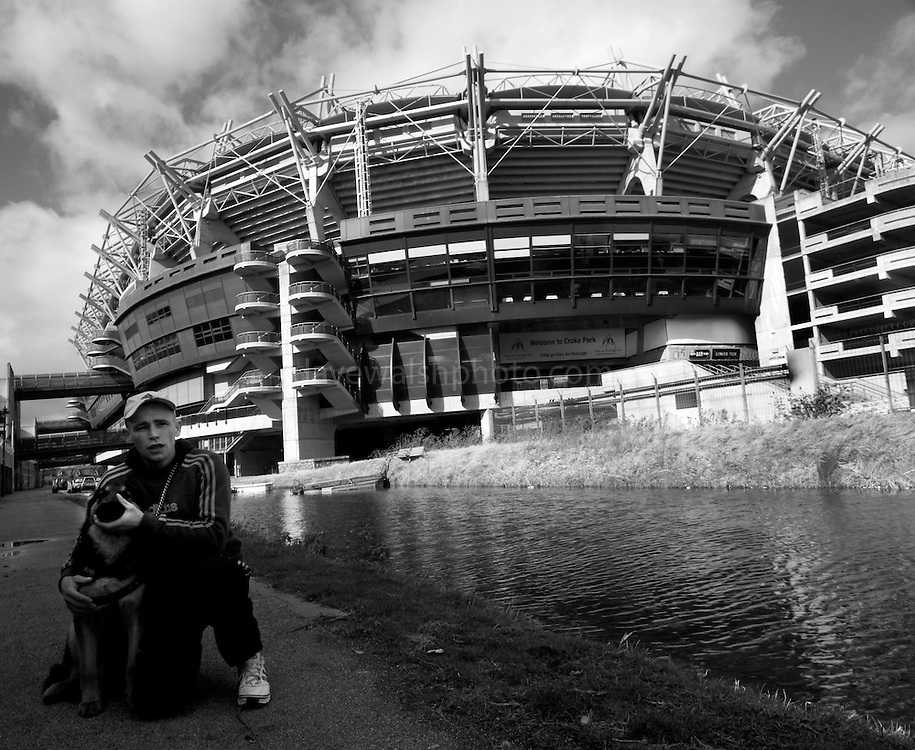 """It's a Friday afternoon. I'm down beside the Royal Canal, taking photos of Croke Park, the Irish gaelic sports stadium. ..A bloke with a dog walks past. ..""""Hey mister, can you take pictures of dogs with that camera?""""..""""Uh, yeah, I could, I suppose""""..""""Can you take a picture of Max? He's only seven months old, and me last dog was killed by a car.""""..""""Ah. My sister's dog was killed by a car two weeks ago. Staffy-whippet cross""""..""""Right. Very intelligent then"""", taps his head, meaninfully...I get him to write down his address. Hey gets a bit confused doing it. ..""""Sorry man, I had a big operation on my head, and I get mixed  up"""", takes off his baseball cap, shows me criss-cross collection of scars all over his crown and down to his chin. ..When I got Richie and max to stay still long enough, I managed to get some photos. I'm posting them to Richie. Hope he puts them on his wall.."""
