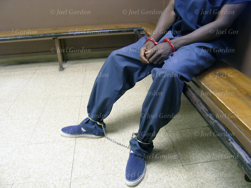 African American inmate in jail booking area, handcuffed and with leg irons waiting to be transported either to court or prison detainees
