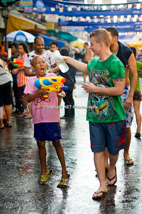 A tourist splash a boy with water during the Songkran festival at Khao San road, a popular tourist area in Bangkok. Songkran is the traditional Thai New Year festival. The most obvious celebration of Songkran is the throwing of water.