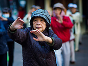 26 DECEMBER 2017 - HANOI, VIETNAM: People do tai chi during a morning fitness and exercise session at Hoan Kiem Lake, in the Old Quarter of Hanoi. Thousands of Vietnamese people line the lake front in the early hours of the morning to perform tai chi and other low impact aerobic workouts.     PHOTO BY JACK KURTZ