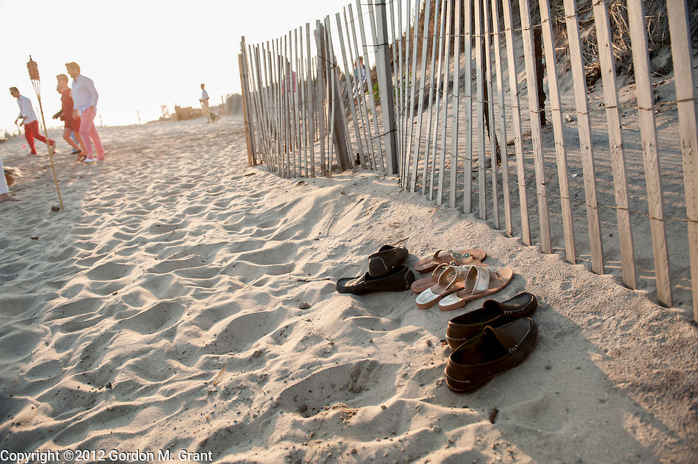 Sagaponack, NY - 6/29/12 - Shoes along a fence during a clambake at Sagg Main Beach in Sagaponack, NY June 29, 2012.     (Photo by Gordon M. Grant)