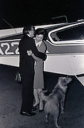 Jimmy and Rosalynn Carter land at a small airport, getting a greeting from the airport dog, at midnight as they end a day of campaigning in Illinois. The frugal candidate used a small twin engine aircraft during the early months of his 1976 presidential campaign. - To license this image, click on the shopping cart below -