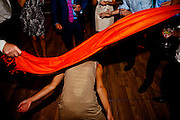 A woman passes under a makeshift limbo stick at a wedding reception in Santa Rosa, California.