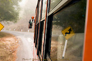 A rural passenger bus destined for Chiang Mai is driving on a foggy and winding road near Pai, Thailand.