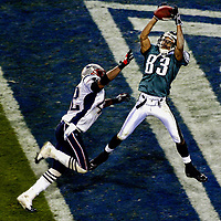 Philadelphia Eagles wideout Greg Lewis makes a 30-yard touchdown reception under pressure from New England Patriots safety Dexter Reid in the 4th quarter of Super Bowl XXXIX at Alltel Stadium in Jacksonville, Florida on Feb. 6, 2005. It was Lewis' first career touchdown in the NFL.