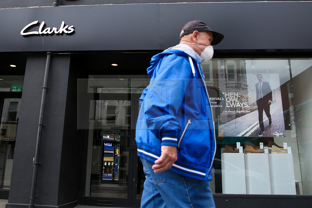 © Licensed to London News Pictures. 22/05/2020. London, UK. A man wearing a face covering walks past a branch of Clarks, UK shoe retailer, in Wood Green, north London. The company announced that it is to lose 900 jobs as it adapts to the challenges posed by the coronavirus crisis. Photo credit: Dinendra Haria/LNP