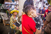 "03 OCTOBER 2012 - BANGKOK, THAILAND: A woman carries her sleeping baby while she shops in Khlong Toey Market in Bangkok. Khlong Toey (also called Khlong Toei) Market is one of the largest ""wet markets"" in Thailand. Thousands of people shop in the sprawling market for fresh fruits and vegetables as well meat, fish and poultry every day.     PHOTO BY JACK KURTZ"