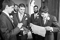 One guy holds the instructions as the others assist the youngest groomsmen how to properly fold his pocket square.