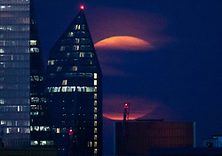 © Licensed to London News Pictures. 15/08/2019. London, UK. Cloud partially covers the Sturgeon full moon as it rises past the Scalpel skyscraper in London. The August full moon is known as the Sturgeon Moon because native American indians believed that the sturgeon fish could most easily be caught at that time. Photo credit: Peter Macdiarmid/LNP