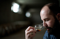 1-7-13---- Balcones Distillery owner Chip Tate noses a whisky in Balcones Distillery warehouse in Waco, Texas.