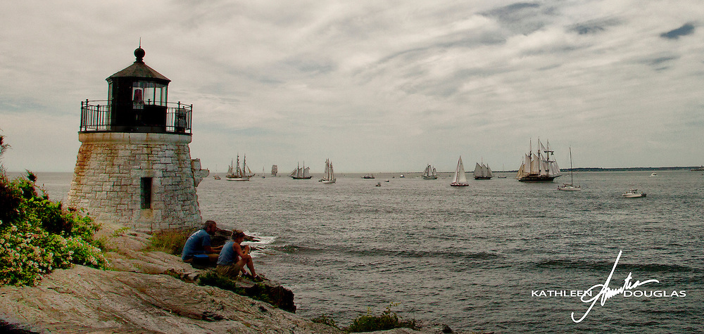 A couple looks on as the Tall Ships muster in the background just beyond the Castle Hill Lighthouse at the mouth of Newport Harbor.