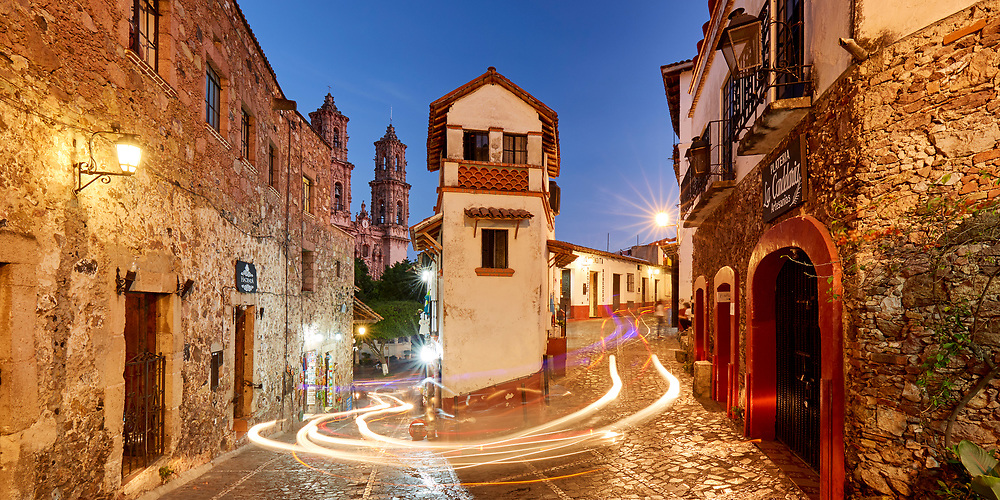 Taxco's taxis leave light trails as they navigate the narrow corner of Guillermo Spratling and Palma at dusk.
