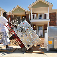 Adam Robison | BUY AT PHOTOS.DJOURNAL.COM<br /> William Barnes, of Memphis, a sub-contract worker with GE, moves as new washer into one of the newly renovated apartments at Barley Court In Verona on Monday.