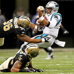 January 1, 2012; New Orleans, LA, USA; New Orleans Saints defensive tackle Tom Johnson (96) and linebacker Martez Wilson (95) tackle Carolina Panthers quarterback Cam Newton (1) during the second half of a game at the Mercedes-Benz Superdome. The Saints defeated the Panthers 45-17. Mandatory Credit: Derick E. Hingle-US PRESSWIRE