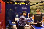 Travelex bureau de change assistant serves currency to passenger at Heathrow airport's terminal 5