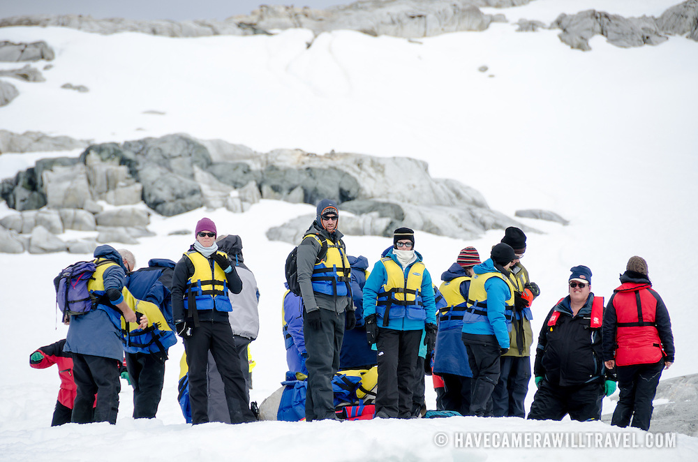 A group of Antarctic tourists ashore at Petermann Island in their life vests waiting to be picked up by zodiacs and transported back to the ship.