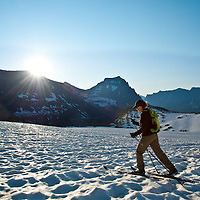 sun rising over mountains in glacier national park woman skiing