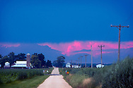 Ominous storm clouds build on the horizon as the last light of the day colors the tall thunderheads a shade of pink.