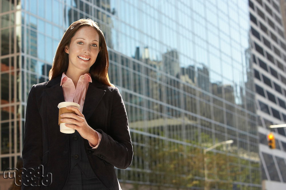 Office worker with drink outside office building portrait