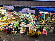 "12 JANUARY 2016 - BANGKOK, THAILAND:      A shopper at a vegetable stand in Khlong Toey Market in Bangkok. Khlong Toey (also called Khlong Toei) Market is one of the largest ""wet markets"" in Thailand. The market is located in the midst of one of Bangkok's largest slum areas and close to the city's original deep water port. Thousands of people live in the neighboring slum area. Thousands more shop in the sprawling market for fresh fruits and vegetables as well meat, fish and poultry.         PHOTO BY JACK KURTZ"