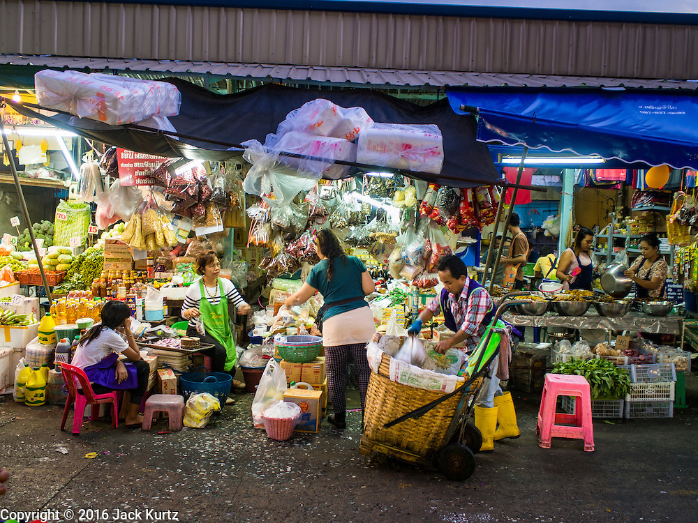 """12 JANUARY 2016 - BANGKOK, THAILAND:      A shopper at a vegetable stand in Khlong Toey Market in Bangkok. Khlong Toey (also called Khlong Toei) Market is one of the largest """"wet markets"""" in Thailand. The market is located in the midst of one of Bangkok's largest slum areas and close to the city's original deep water port. Thousands of people live in the neighboring slum area. Thousands more shop in the sprawling market for fresh fruits and vegetables as well meat, fish and poultry.         PHOTO BY JACK KURTZ"""