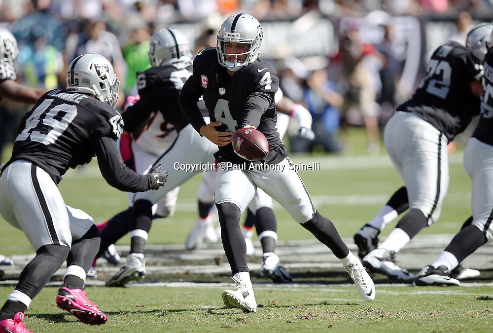 Oakland Raiders quarterback Derek Carr (4) hands off the ball on a running play to Oakland Raiders running back Jamize Olawale (49) during the 2015 NFL week 5 regular season football game against the Denver Broncos on Sunday, Oct. 11, 2015 in Oakland, Calif. The Broncos won the game 16-10. (©Paul Anthony Spinelli)