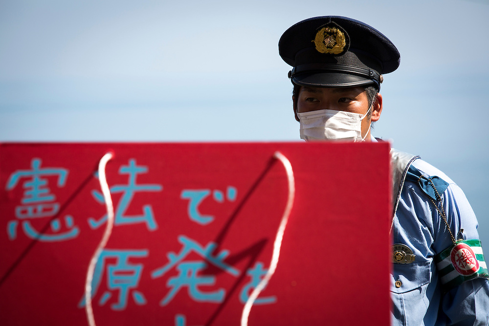 EHIME, JAPAN - AUGUST 12 : Police guard the anti-nuclear protesters who gather in front of Ikata Nuclear Power Plant to protest against the restarting of a nuclear reactor on August 12, 2016 in Ikata, Ehime prefecture, northwestern Shikoku, Japan. The Shikoku Electric Power Company restarted the plant's No.3 reactor at around 9 AM on Friday. It is the third plant to go online under new regulations issued after the Fukushima Daiichi nuclear disaster. (Photo by Richard Atrero de Guzman/NURPhoto)