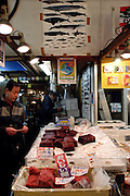 "A wholesaler at the world's biggest fish Market in Tsukiji, Tokyo displays pieces of whale meat at his store at the market. More than 2,300 tons of fish -- about one-third of the total consumed in Japan -- passes through Tsukiji each day and the market offers more than 450 varieties of marine products. The market, which dates back almost 75 years, is slated to move to a high-tech site on a man-made island in Toyosu, which is well-documented as being contaminated with benizine. Not that Tsukiji is much better off -- many buildings in the aging site are stuffed with asbestos. ""Choose your poison,"" says one Tsukiji official. The new site, which the government plans to be readied by 2012, will be significantly larger, with more room for off-loading and for sellers to display their goods. The current location, says one official, is too cramped and collisions between motorised carts and pedestrians means accidents occur almost daily. Meanwhile, with fish sales down, it is becoming more difficult to justify Tsukiji's prime location and property developers are keeping a close watch on Tsukiji land, which is just a few blocks from the ritzy Ginza district of Tokyo, where per-meter land prices are among the highest in the world...The move to the new Toyosu location, meanwhile, has been at the center of heated debate -- clean-up operations alone are estimated to cost ¥67 billion (around US$660 million), with a further ¥450 billion to build a new marketplace. Big wholesalers favour the move, but the 1,600-plus merchants mostly are against it. Yoshiharu Kikuraku, a Tsukiji storeowner who began working at the market 60 years ago, expresses bewilderment at the plans, saying that the name Tsukiji itself has become synonymous with the world's best and most eclectic selection of fish. ""This place has a long tradition. Why break it and start from scratch all over again?"" he says. ""Government officials only think what's best for themselves, nobody else."" Indeed, many companies dealing"