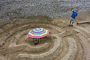 Sandy maze built on low-tide River Thames foreshore during Thames Festival on London's South Bank event.