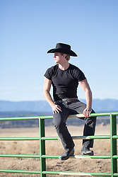 cowboy sitting on a ranch fence with mountain views