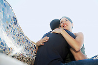 Young couple hugging on stone bench portrait low angle view