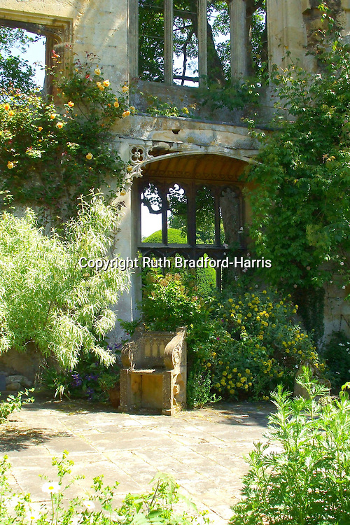 A Gothic Cotswold stone seat and tiers of Gothic tracery windows in a courtyard in the abbey ruins at Sudeley Castle, Gloucestershire. <br /> <br /> The courtyard has been planted with yellow-flowering plants and shrubs which, coupled with the honey-coloured Cotswold stone, make for a glowing golden garden in the June sunlight.<br /> <br /> Date taken: 21 June 2010.