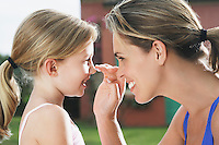 Mother applying sunscreen on daughter's (5-6) nose smiling side view profile
