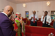 Elder Young performs a communion service at the First Church of American Slaves at 314 Dr. W. J. Hodge Street, Sunday Aug. 7, 2011 in Louisville, Ky. To the left is Kevin Rickman, Elder Young, author Norris Shelton and Dereck Barber, Vice President of ASI. (Photo by Brian Bohannon)