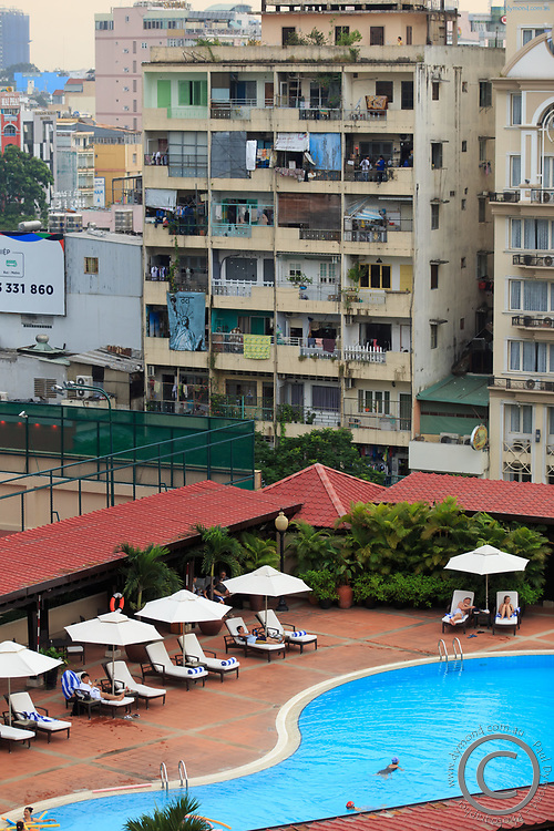 A luxury hotel pool below crowded apartment buildings in District 1, Ho Chi Minh City, Vietnam