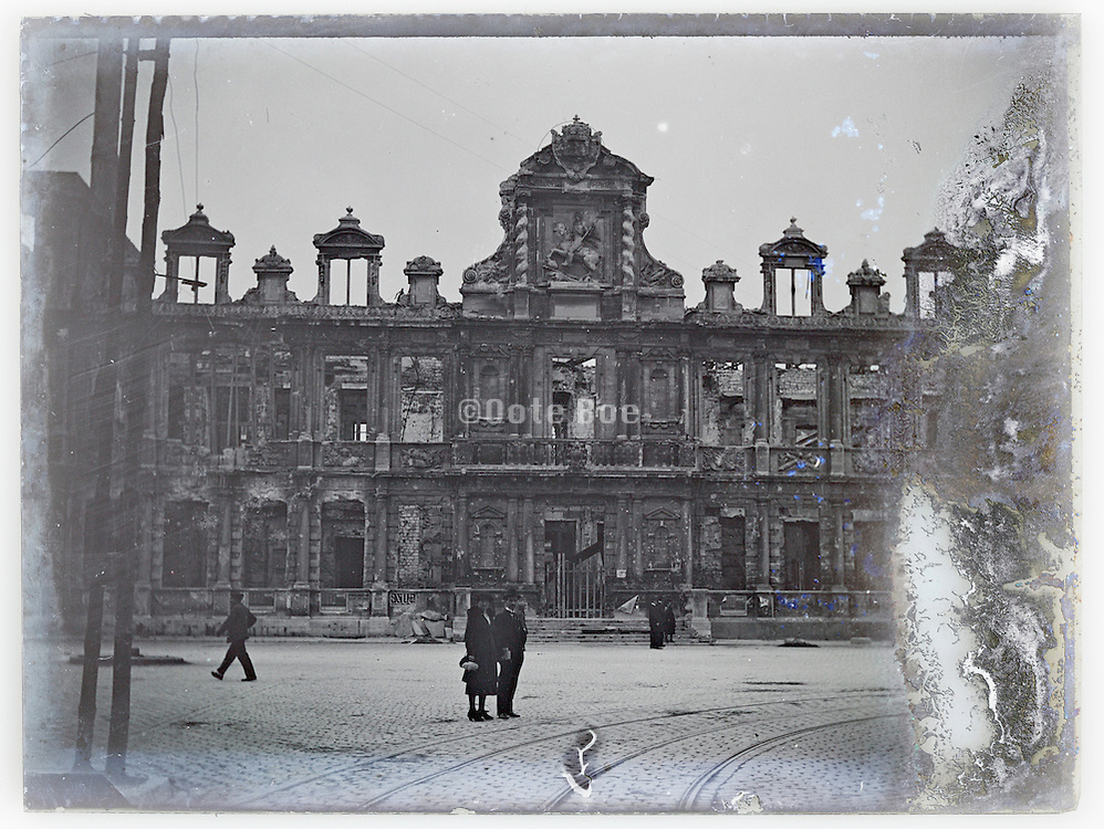 eroding glass plate with two people standing in front of a ruined building