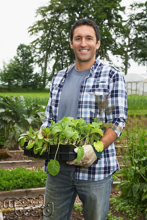 Man carrying plants in field portrait
