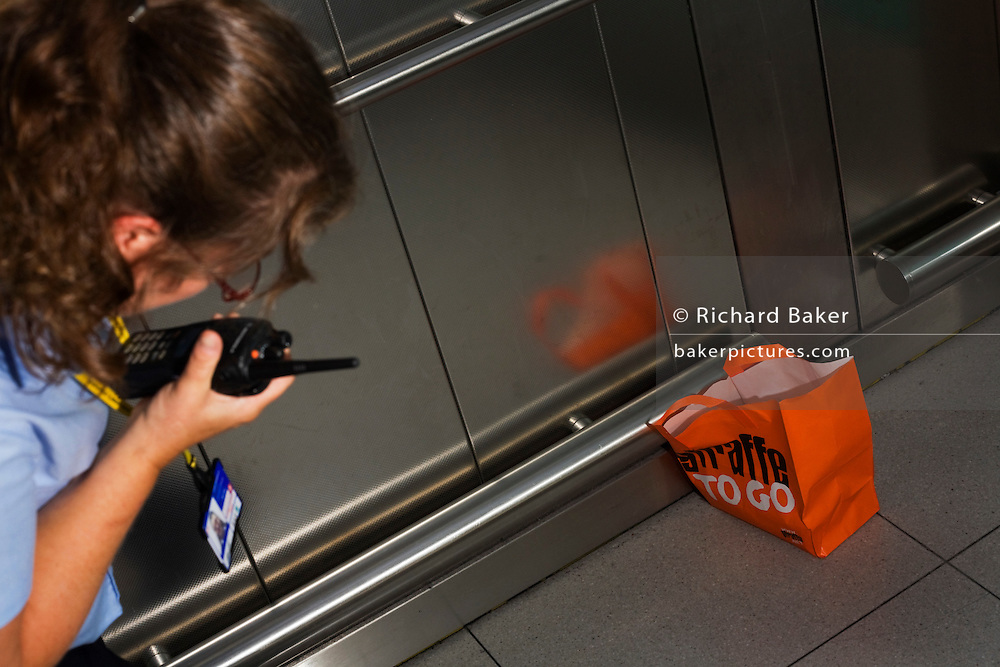 "A female security officer has spotted an abandoned bag with the words 'Giraffe To Go' on the side, inside a lift of Heathrow airport's Terminal 5. The woman talks urgently but calmly using her walkie-talkie. She needs to report it to her controllers as a suspicious package but may turn out to be an innocent lunch bag left by a hurrying and absent-minded passenger, realising their flight is about to close, instead of a bomb left by a malicious terrorist. The lady bends down to give as accurate description as she can before airport police arrive to determine how serious the treat is and possibly order a costly evacuation. From writer Alain de Botton's book project ""A Week at the Airport: A Heathrow Diary"" (2009)."