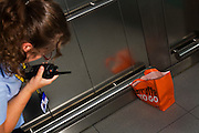 """A female security officer has spotted an abandoned bag with the words 'Giraffe To Go' on the side, inside a lift of Heathrow airport's Terminal 5. The woman talks urgently but calmly using her walkie-talkie. She needs to report it to her controllers as a suspicious package but may turn out to be an innocent lunch bag left by a hurrying and absent-minded passenger, realising their flight is about to close, instead of a bomb left by a malicious terrorist. The lady bends down to give as accurate description as she can before airport police arrive to determine how serious the treat is and possibly order a costly evacuation. From writer Alain de Botton's book project """"A Week at the Airport: A Heathrow Diary"""" (2009)."""