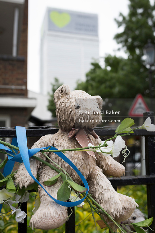 Childrens' bears and cuddly toys on railings near where the Grenfell fire occured, on the first anniversary of the tower block disaster, on 14th June 2018, in London, England. 72 people died when the tower block in the borough of Kensington & Chelsea were killed in what has been called the largest fire since WW2. The 24-storey Grenfell Tower block of public housing flats in North Kensington, West London, United Kingdom. It caused 72 deaths, out of the 293 people in the building, including 2 who escaped and died in hospital. Over 70 were injured and left traumatised. A 72-second national silence was held at midday, also observed across the country, including at government buildings, Parliament.