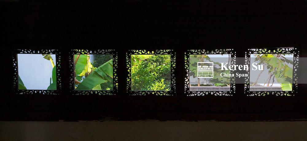 View of garden through window inside traditional architecture in the water town, Zhujiajiao, near Shanghai, China
