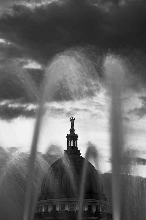 The dome of the Wisconsin State Capitol is pictured looking through a water fountain atop the Monona Terrace Community and Convention Center in downtown Madison, Wis., during a summer sunset on Sept. 6, 2015. (Photo by Jeff Miller - www.jeffmillerphotography.com)
