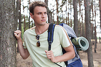 Handsome young man with backpack hiking in forest