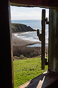 "In Sandy Cove, pictured through a blockhouse window of Fort Ross, the Russian-American Company made the first four ships built in (Alta) California. Fort Ross State Historic Park preserves a former Russian colony (1812-1842) on the west coast of North America, in what is now Sonoma County, California, USA. Visit Fort Ross and dramatic coastal scenery 11 miles north of Jenner on California Highway One.  Initially, sea otter pelts funded Russian expansion, but by 1820, overhunting motivated the Russian-American Company to introduce moratoriums on hunting seals and otters, the first marine-mammal conservation laws in the Pacific. Russian voyages greatly expanded California's scientific knowledge. For centuries before Europeans arrived, this site was called Metini and had been occupied by the Kashaya band of Pomo people who wove intricate baskets and harvested sea life, plants, acorns, deer, and small mammals. Sponsored by the Russian Empire, ""Settlement Ross"" was multicultural, built mostly by Alaskan Alutiiq natives and occupied mostly by native Siberians, Alaskans, Hawaiians, Californians, and mixed Europeans. Renamed ""Ross"" in 1812 in honor of Imperial Russian (Rossiia), Fortress Ross was intended to grow wheat and other crops to feed Russians living in Alaska, but after 30 years was found to be unsustainable. Fort Ross was sold to John Sutter in 1841, and his trusted assistant John Bidwell transported its hardware and animals to Sutter's Fort in the Sacramento Valley. Fort Ross is a landmark in European imperialism, which brought Spanish expanding west across the Atlantic Ocean and Russians spreading east across Siberia and the Pacific Ocean. In the early 1800s, Russians coming from the north met Spanish coming from the south along the Pacific Coast of California, followed by the USA arriving from the east in 1846 for the Mexican-American War. Today, Fort Ross is a California Historical Landmark and a National Historic Landmark."