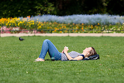 © Licensed to London News Pictures. 12/05/2016. LONDON, UK.  A woman relaxes on the grass during warm sunny weather in St James's Park at lunchtime.  Photo credit: Vickie Flores/LNP
