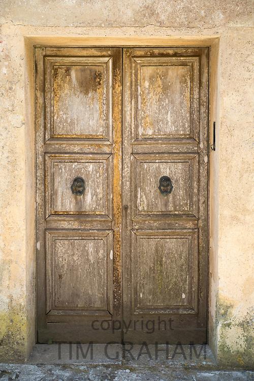 Quaint old weather-beaten wooden double door and doorway in historic centre of Erice, Sicily, Italy