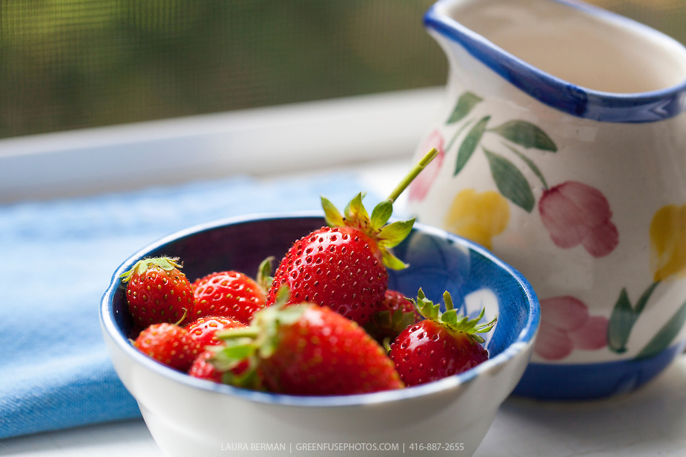 A small blue and white bowl of very ripe, red strawberries with a jug of cream on a white surface with a blue cloth.
