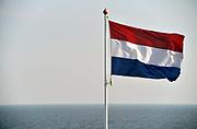Nederland, Afsluitdijk, 22-2-2018 Nederlandse vlag wappert bij het monument van de afsluiting. Op de achtergrond het IJsselmeer. Foto: Flip Franssen